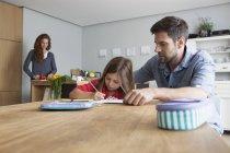 Маленькая девочка делает домашнее задание за кухонным столом, пока ее отец смотрит на нее — стоковое фото