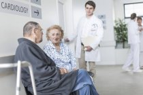 Elderly patients sitting and waiting in hospital — Stock Photo