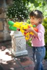 Smiling little girl playing with water gun — Stock Photo