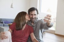 Mature couple sitting on floor taking selfie with smart phone — Stock Photo