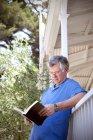 Mann gelehnt Balustrade ein Buch zu lesen — Stockfoto