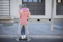 Pareja joven con monopatín abrazándose en la calle - foto de stock