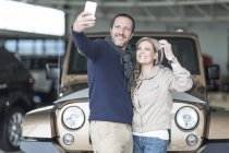 Happy couple at car dealership taking selfie in front of new car — Stock Photo