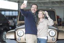 Casal feliz na concessionária tendo selfie na frente do carro novo — Fotografia de Stock