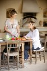 Two female friends preparing vegetables in the kitchen — Stock Photo
