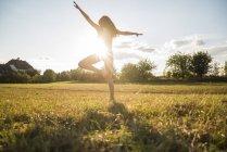 Visão traseira da mulher de pé em uma perna em um prado no backlight — Fotografia de Stock