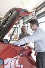Concessionnaire automobile expliquant la nouvelle voiture pour jeune femme — Photo de stock