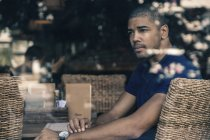 Man in a cafe behind windowpane — Stock Photo