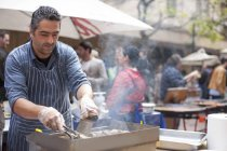 Человек, жарки мяса на рынке города — стоковое фото