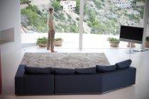 Spanien, Mallorca, Mann steht in seinem Wohnzimmer und schaut aus dem Fenster — Stockfoto