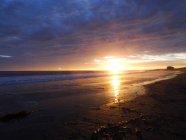 Vista distante da praia de areia e céu nublado ao pôr do sol — Fotografia de Stock