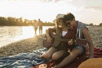 Young couple with guitar relaxing at the riverside at sunset with friends on background — Stock Photo
