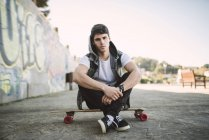 Portrait of serious looking young man sitting on his longboard — Stock Photo