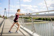 Giovane atleta che si estende sul ponte — Foto stock