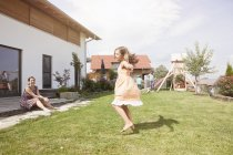 Playful caucasian girl with family in garden — Stock Photo