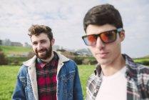 Ritratto di giovane uomo sorridente con il suo amico indossa specchio Occhiali da sole in primo piano — Foto stock