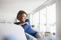 Smiling woman at home sitting on couch — Stock Photo