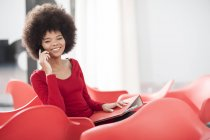 Young woman in office sitting on red chair talking on cell phone — Stock Photo