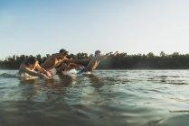 Happy friends splashing in river in summer — Stock Photo