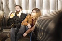 Couple with beer bottle relaxing in garage — Stock Photo