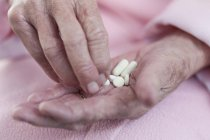 Mãos de mulher sênior segurando pílulas — Fotografia de Stock