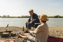 Senior couple barbecueing sausages on the beach — Stock Photo