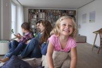 Portrait d'une fillette souriante sur le dossier du canapé avec sa famille assis dans le fond — Photo de stock