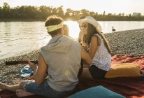 Friends with guitar relaxing at the riverside at sunset — Stock Photo