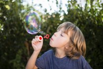 Blond little boy blowing soap bubble — Stock Photo