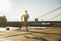 Young man running by the riverside — Stock Photo