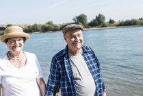 Retrato de la feliz pareja senior en riverside - foto de stock