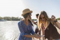 Happy friends having fun at river in summer — Stock Photo