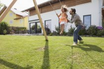 Father pushing daughter on swing in garden — Stock Photo