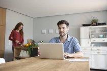 Uomo a casa usando il portatile con donna in verdure di taglio di sfondo — Foto stock