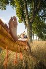 Жінка з навушниками лежить в гамаку відпочинку на природі — стокове фото