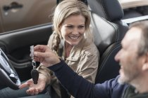 Man sitting in car handing over key to smiling woman — Stock Photo
