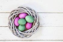 Вид сверху на зеленые и розовые пасхальные яйца в гнезде — стоковое фото