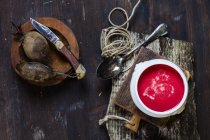 Top view of beetroot soup in bowl  on cutting board — Stock Photo