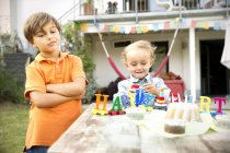 Happy toddler celebrating birthday in garden with displeases brother standing besides — Stock Photo