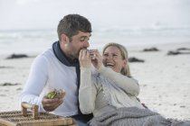 Laughing couple having picnic on a beach — Stock Photo