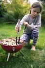 Chica barbacoa salchichas y carne en jardín - foto de stock