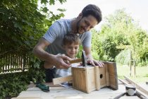 Caucasian father and son timbering a birdhouse — Stock Photo