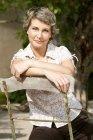 Ritratto di donna matura sorridente che si appoggia sullo schienale di una sedia da giardino — Foto stock