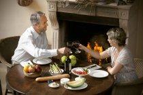 Älteres paar sitzen am gedeckten Tisch Toasten mit Rotwein vor offenem Feuer — Stockfoto