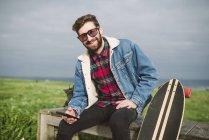 Giovane hipster seduto nel parco con longboard e smartphone in mano — Foto stock