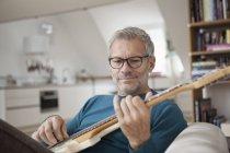 Зріла людина вдома грав на гітарі — стокове фото
