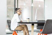 Lächelnde junge Frau sitzt im Büro — Stockfoto