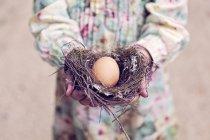 Girl holding easter egg in nest — Stock Photo