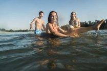 Amis heureux avec chambre à air et boule dans l'eau — Photo de stock
