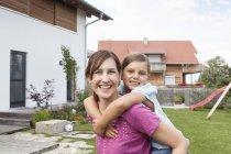 Retrato de sonriente madre con hija reemplazo en jardín - foto de stock